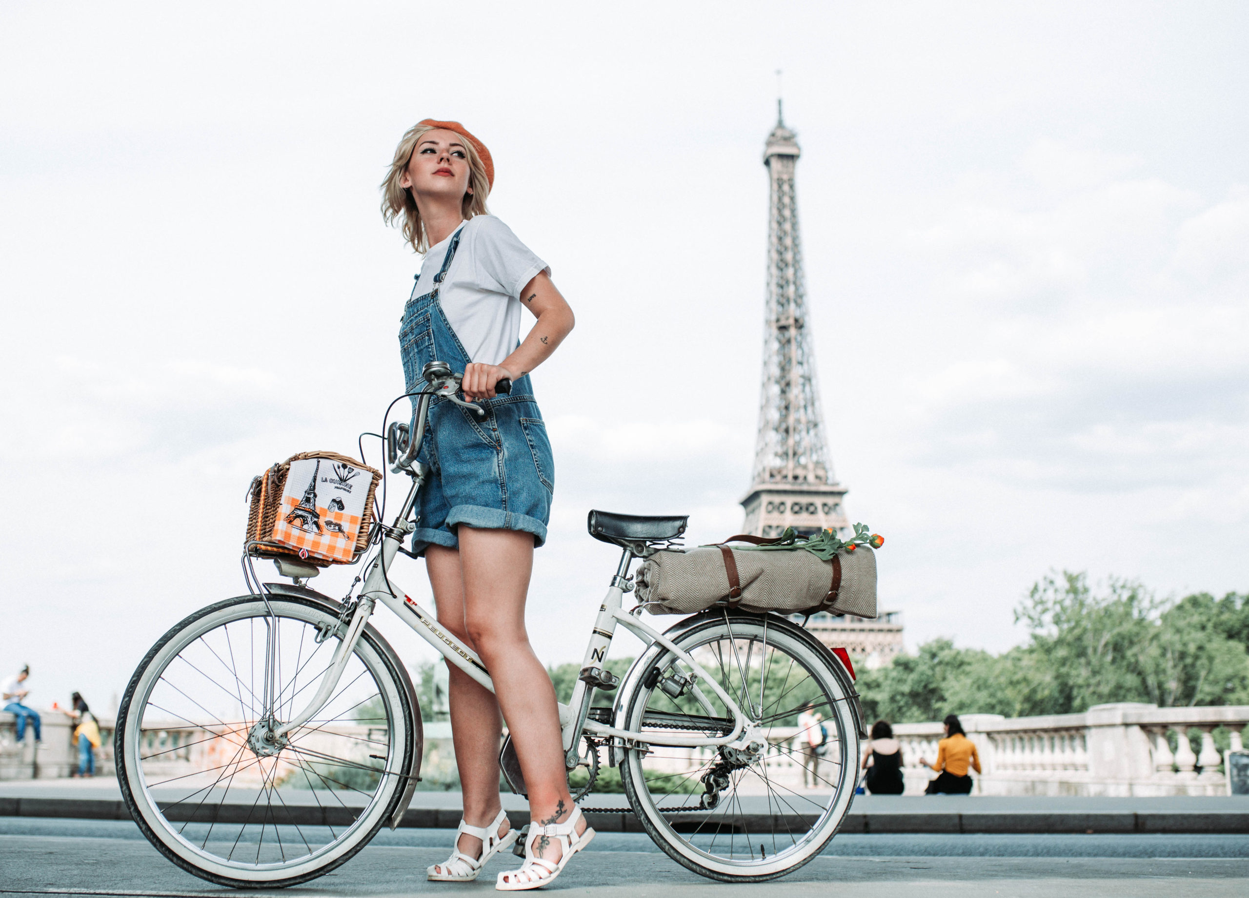 A woman standing still on a bicycle in front of the Eiffel Tower