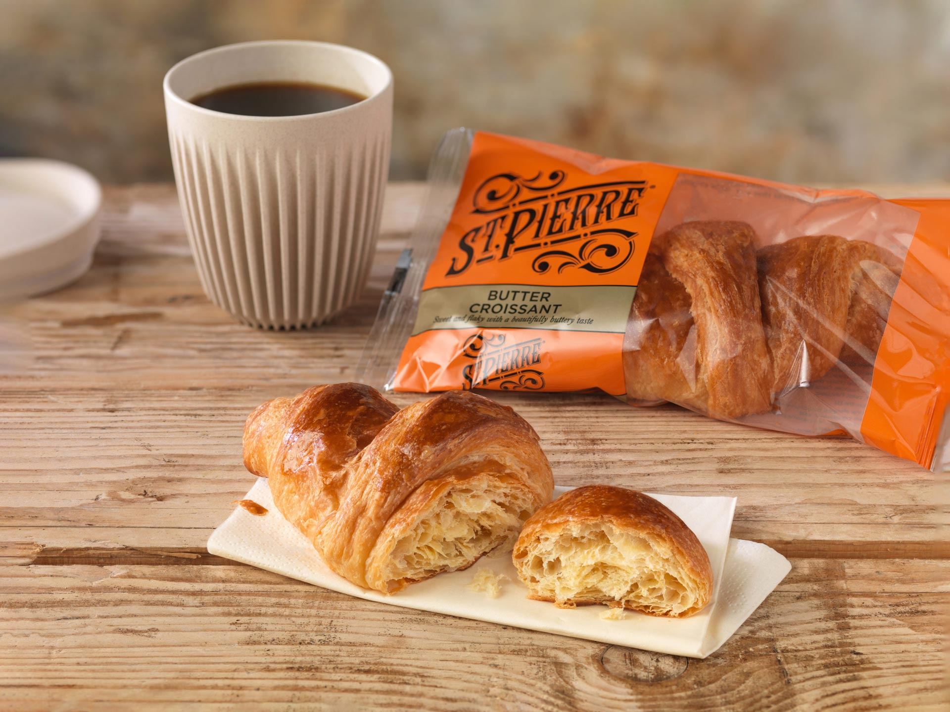 A croissant cut in half on a paper napkin on a wooden table next to a croissant in pack and a black coffee