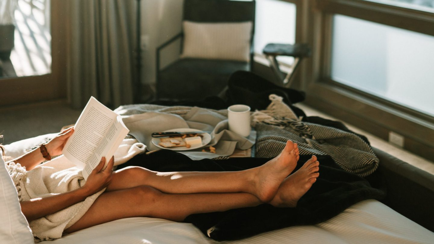 Woman reading on bed with breakfast on tray next to her