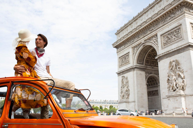 A couple in an orange car by the Arc de Triomphe in Paris