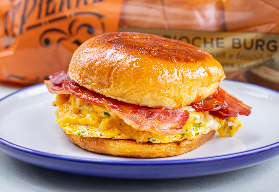 A photo of a Brioche French Toast Cheese and Bacon Roll recipe on a white and blue plate with St Pierre Brioche Burger Buns in the background