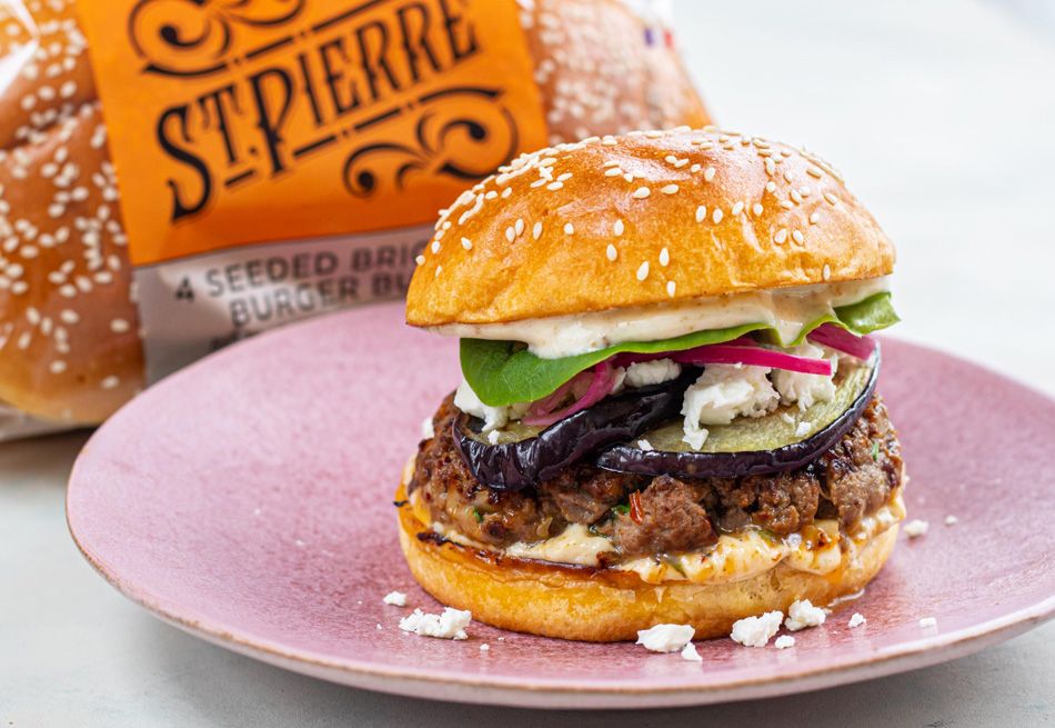 A Cumin Lamb and Aubergine BBQ Burger on a pink plate, placed on a white table with St Pierre burger buns in the background