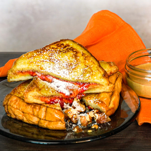 A photo of a peanut butter and strawberry jam French toast sandwich on a glass plate with an orange napkin and jar of peanut butter next to it