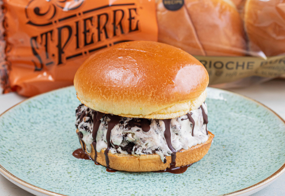 A No-Churn Cookies & Cream Ice Cream Burger recipe on a blue plate with St Pierre Burger Buns in the background