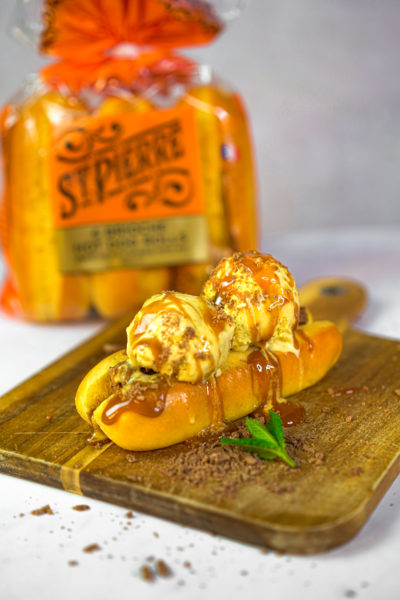 A photo of a brioche hot dog roll on a wooden board filled with scoops of vanilla ice cream and caramel sauce