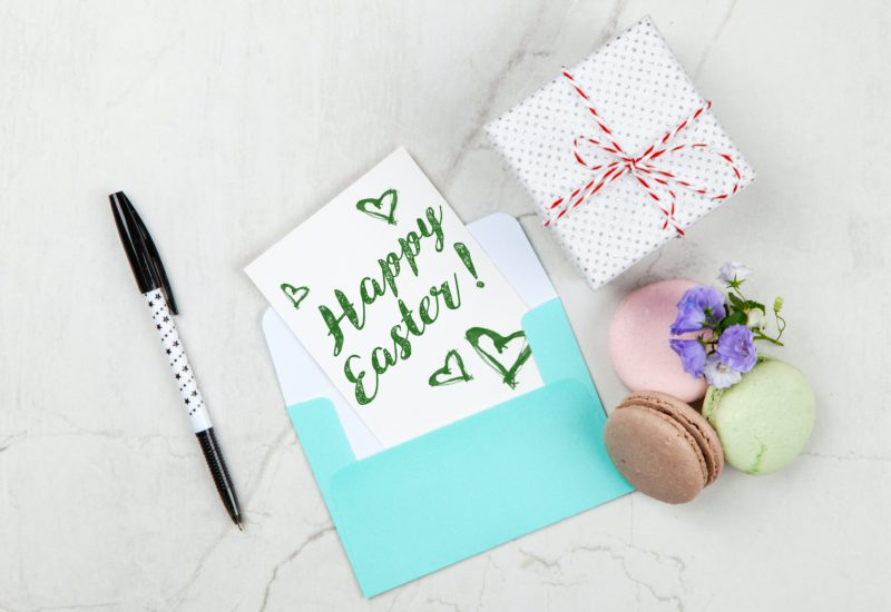 Easter recipe ideas: an overhead photo of a Happy Easter card on a table with macarons and a present box
