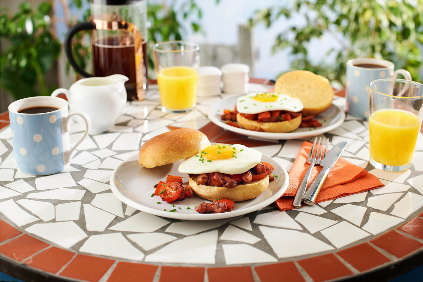 A table with plates and breakfast burgers in an outdoor setting